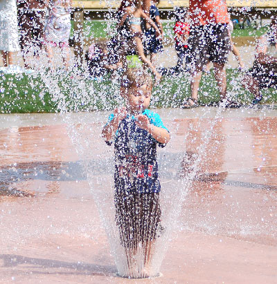 Photo of a young boy standing in spraying water