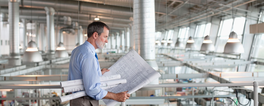 Man looking at blueprints in a new industrial construction