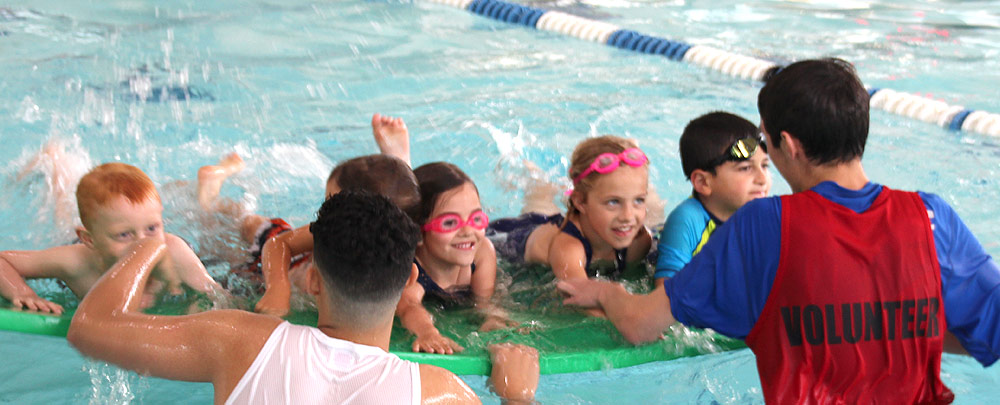 volunteer helping during a swim class with kids splashing in the pool